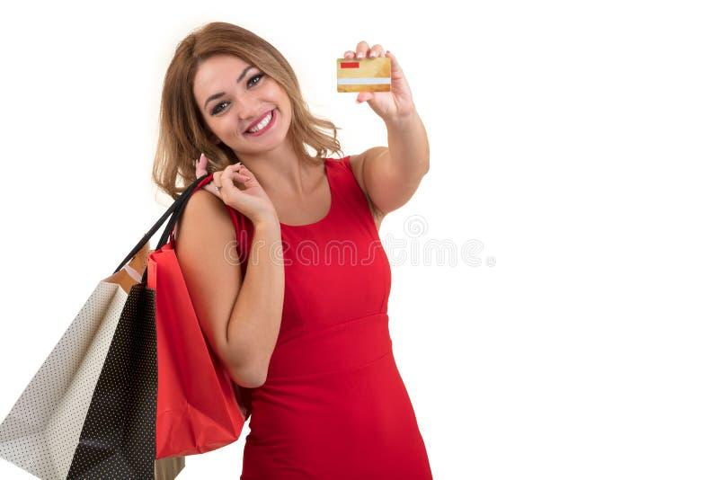 Mujer joven sorprendida emocionada alegre con la tarjeta de crédito sobre el fondo blanco imagen de archivo libre de regalías
