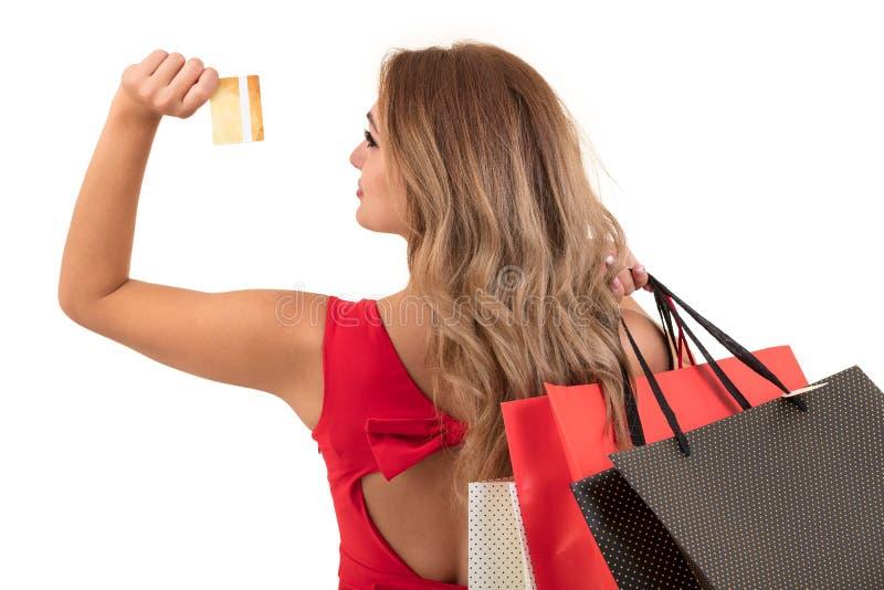 Mujer joven sorprendida emocionada alegre con la tarjeta de crédito sobre el fondo blanco foto de archivo libre de regalías