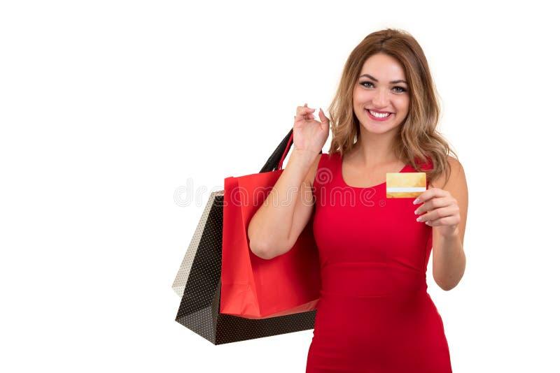 Mujer joven sorprendida emocionada alegre con la tarjeta de crédito sobre el fondo blanco imagen de archivo