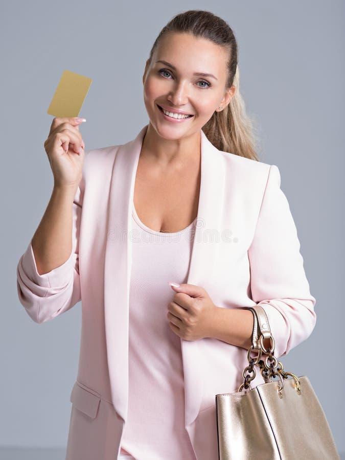 Mujer joven sorprendida emocionada feliz con la tarjeta de crédito aislada imagen de archivo