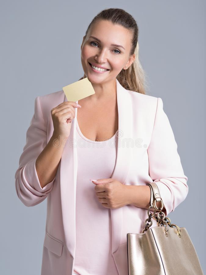 Mujer joven sorprendida emocionada feliz con la tarjeta de crédito aislada imágenes de archivo libres de regalías