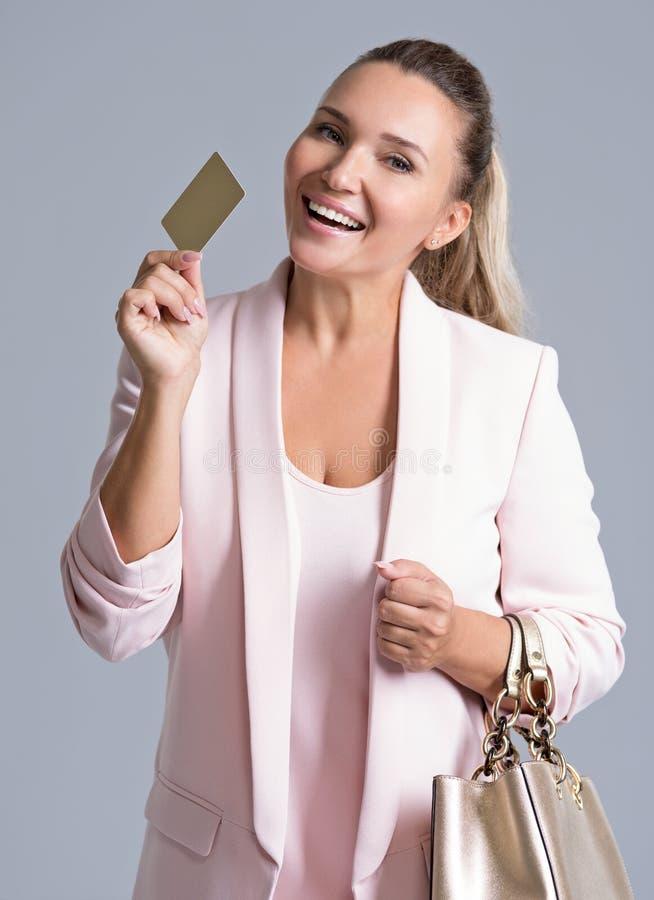 Mujer joven sorprendida emocionada feliz con la tarjeta de crédito aislada imagenes de archivo