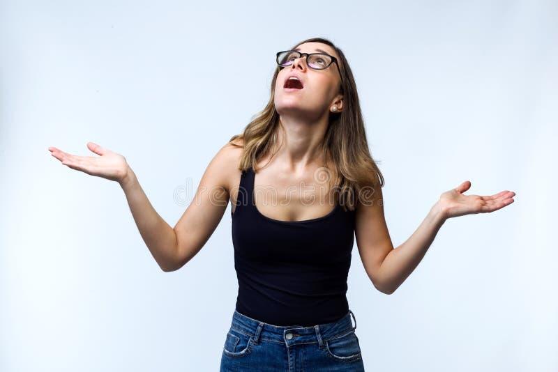 Mujer joven sorprendida hermosa con las lentes que miran al tejado sobre el fondo blanco foto de archivo