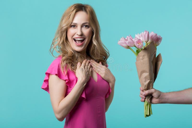 Mujer joven sorprendida que consigue las flores de hombre fotografía de archivo