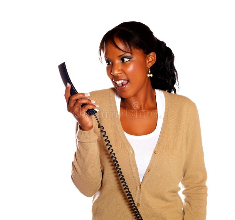 Mujer joven sorprendida que mira para telefonar imagenes de archivo