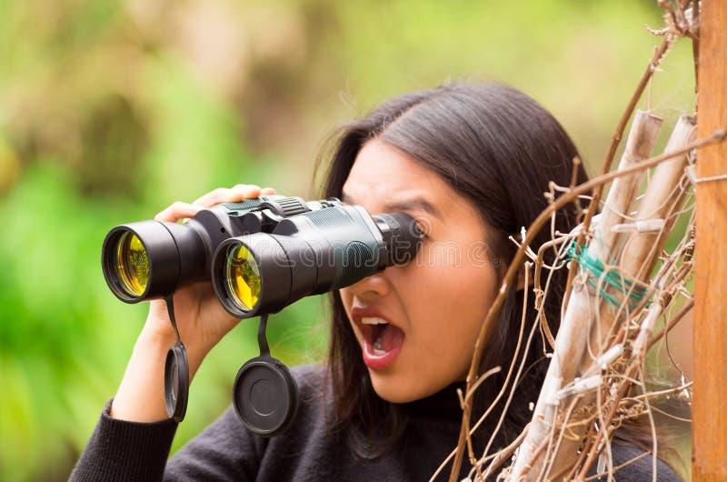 Mujer joven sorprendida que mira a través de los prismáticos negros en el bosque en un fondo borroso foto de archivo