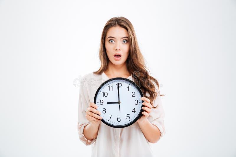 Mujer joven sorprendida que sostiene el reloj fotos de archivo