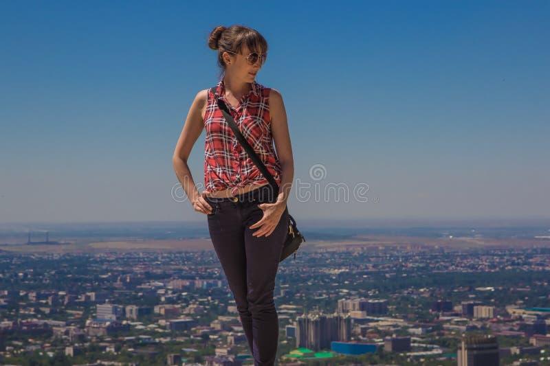 Mujer joven staing en la colina con la opinión de la ciudad, Almaty, Kazakhsta fotos de archivo