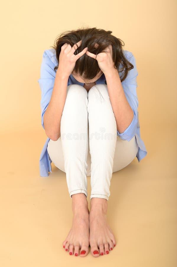 Mujer joven subrayada que se sienta en el piso con la cabeza en manos fotos de archivo libres de regalías