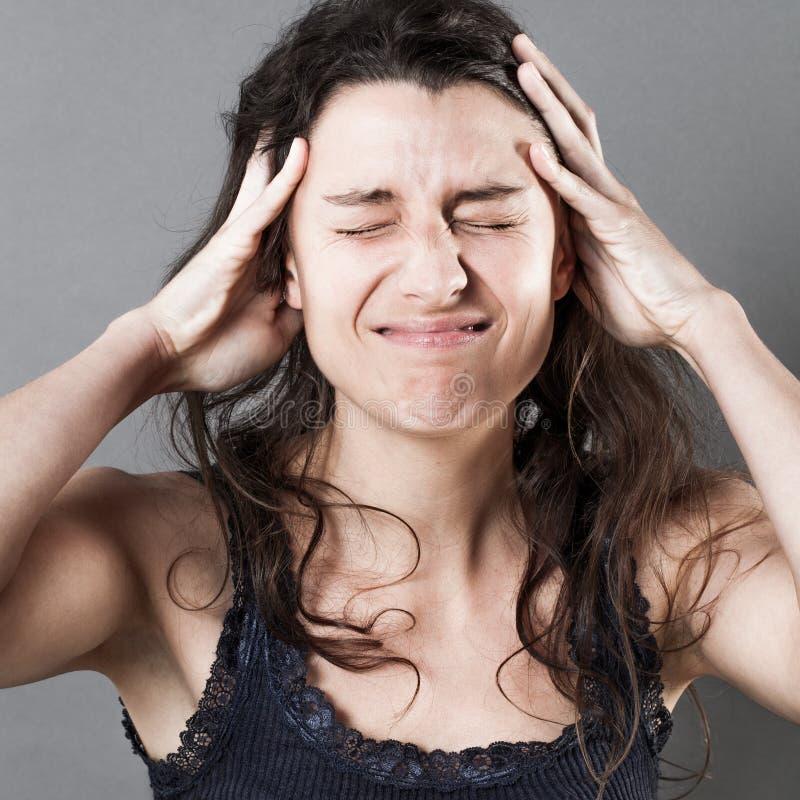 Mujer joven sufridora con las manos en su pelo que tiene dolor de cabeza fotografía de archivo libre de regalías