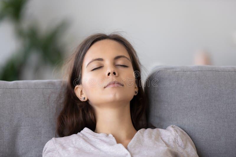 Mujer joven tranquila que se relaja en el sofá cómodo con los ojos cerrados cerca para arriba fotos de archivo