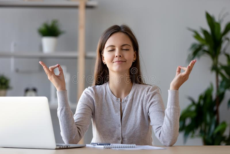 Mujer joven tranquila que toma la rotura que hace ejercicio de la yoga en el lugar de trabajo imagen de archivo libre de regalías
