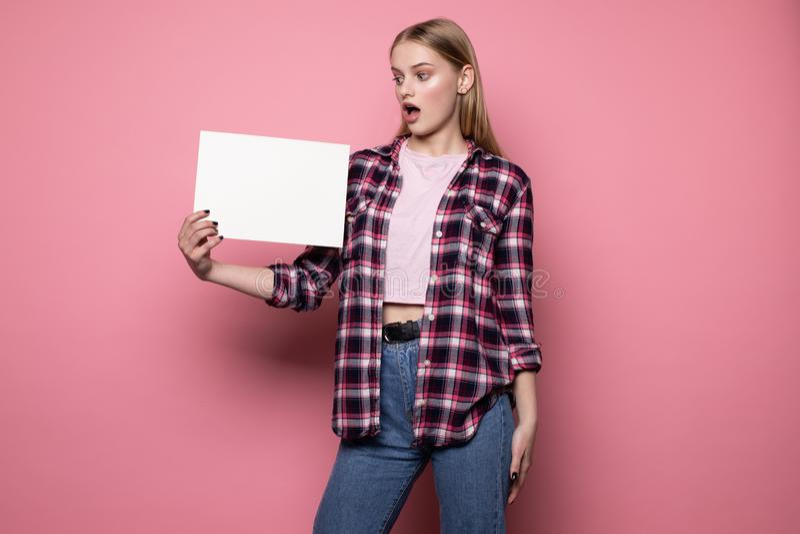 Mujer joven trastornada chocada en la ropa casual, llevando a cabo el espacio en blanco vac?o blanco para su texto imagenes de archivo