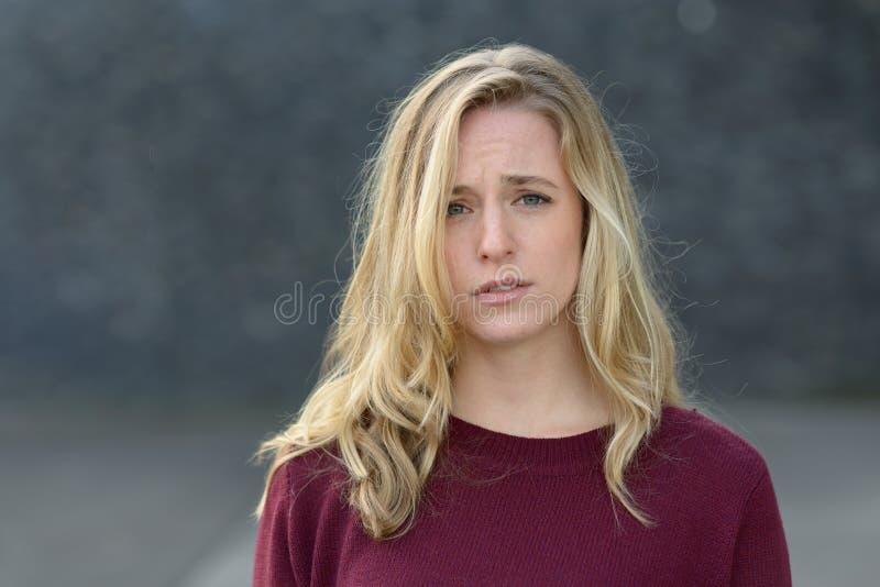 Mujer joven trastornada con una expresión triste foto de archivo
