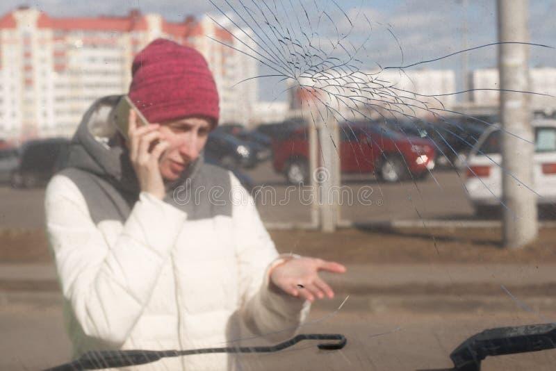 Mujer joven trastornada después de un accidente de tráfico que invita al teléfono imagenes de archivo