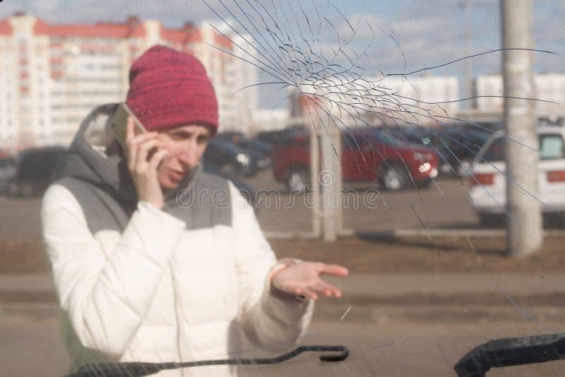 Mujer joven trastornada después de un accidente de tráfico que invita al teléfono foto de archivo libre de regalías