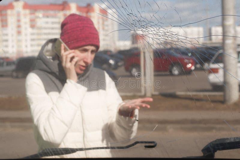 Mujer joven trastornada después de un accidente de tráfico que invita al teléfono imágenes de archivo libres de regalías