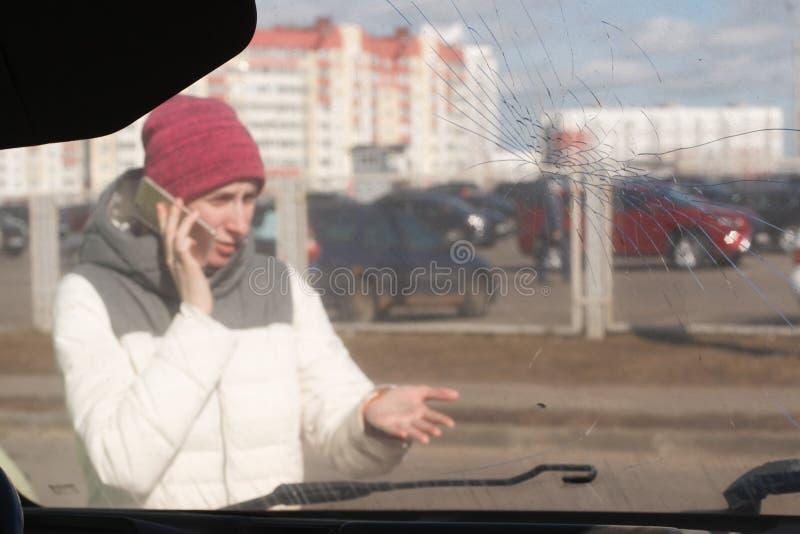 Mujer joven trastornada después de un accidente de tráfico que invita al teléfono fotografía de archivo