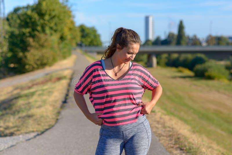 Mujer joven trastornada que mira su grasa del vientre imagen de archivo libre de regalías