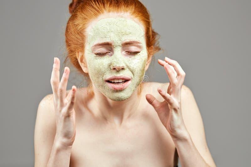Mujer joven triste infeliz enojada con una máscara verde de la arcilla en su cara fotos de archivo libres de regalías
