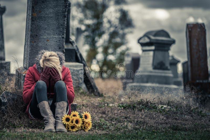 Mujer joven triste sola en el luto delante de una lápida mortuaria foto de archivo
