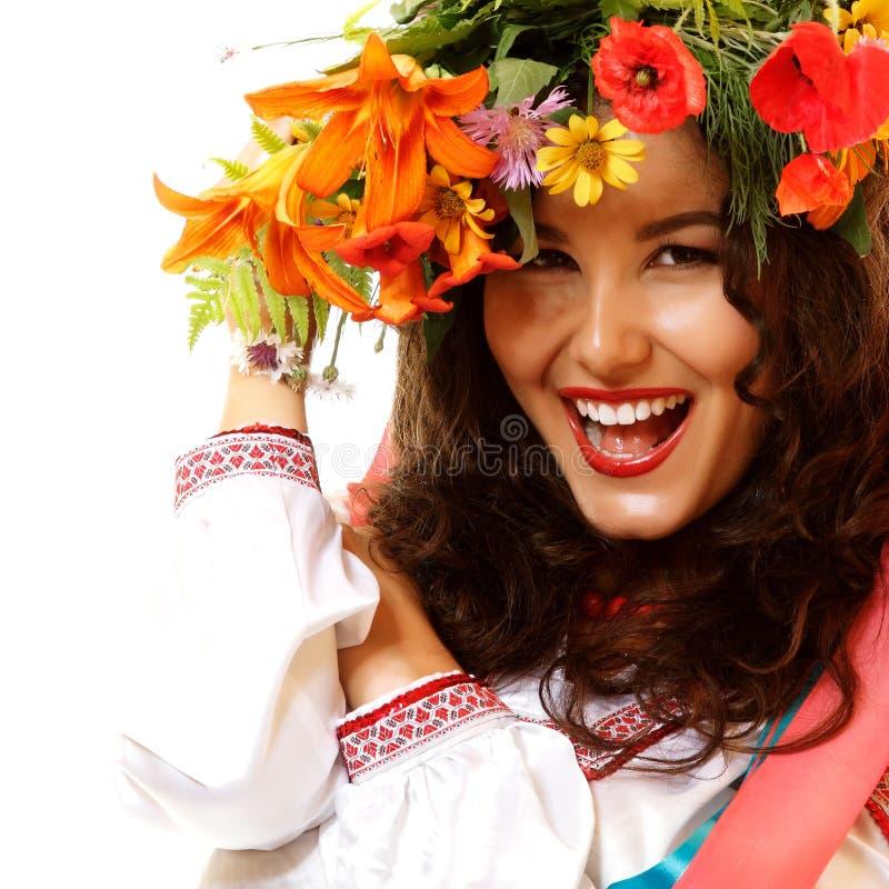 Mujer joven ucraniana hermosa en la guirnalda de las flores del verano y foto de archivo