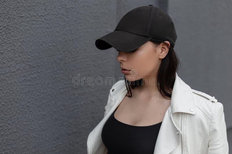 Mujer joven urbana bonita en una gorra de béisbol negra de moda en una chaqueta de cuero blanca de moda en una camiseta cerca de  fotos de archivo