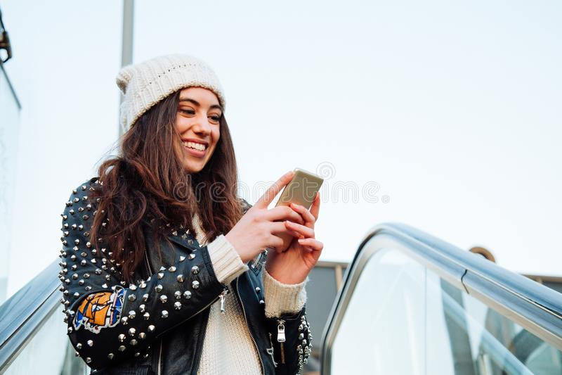 Mujer joven urbana que usa el teléfono en la escalera móvil fotografía de archivo libre de regalías