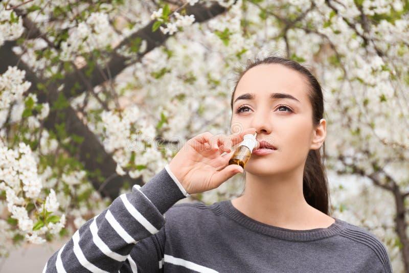 Mujer joven usando descensos nasales cerca del árbol floreciente Concepto de la alergia foto de archivo