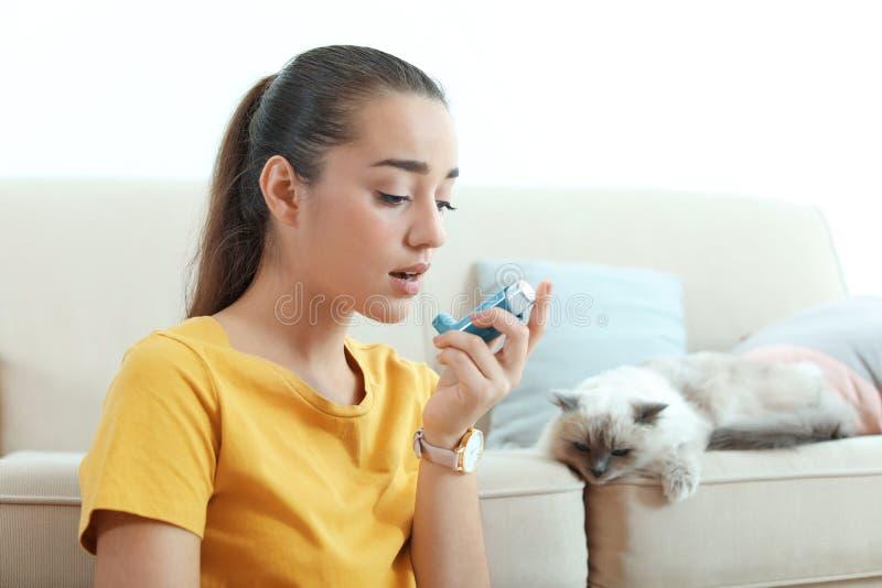 Mujer joven usando el inhalador del asma cerca del gato en casa fotos de archivo
