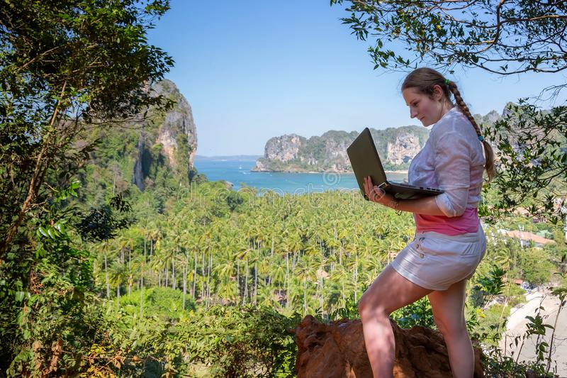 Mujer joven usando el ordenador portátil con el ordenador de Internet 4g en una montaña con la opinión tropical de la playa Traba fotos de archivo