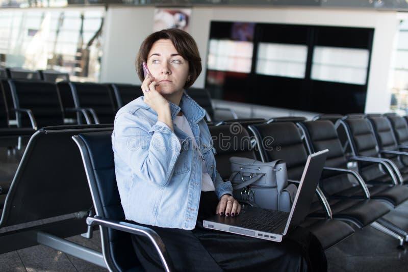 Mujer joven usando el ordenador portátil en el aeropuerto imágenes de archivo libres de regalías