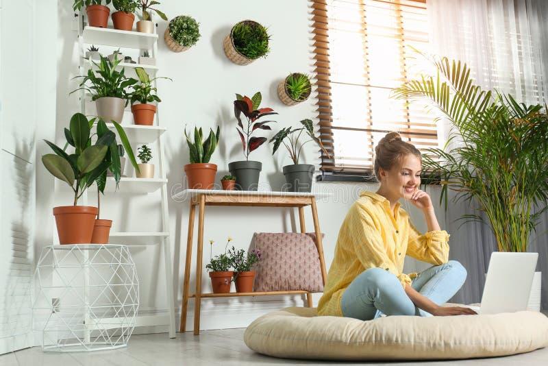 Mujer joven usando el ordenador portátil en sitio con las plantas caseras imagenes de archivo