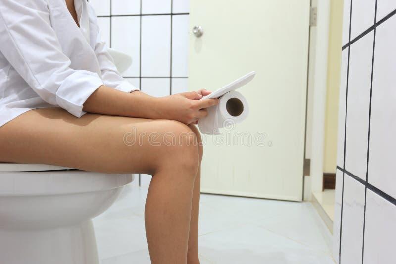 Mujer joven usando el teléfono elegante móvil mientras que se sienta en retrete foto de archivo