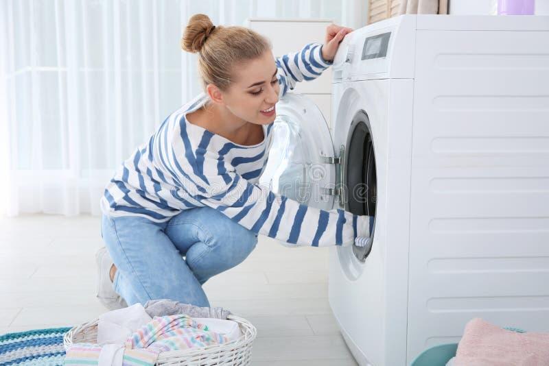 Mujer joven usando la lavadora en casa fotografía de archivo libre de regalías