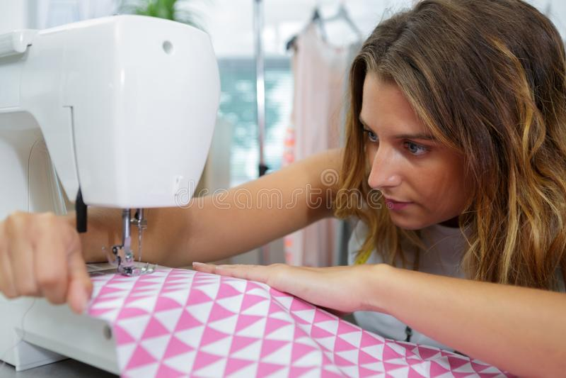 Mujer joven usando la máquina de coser imagen de archivo