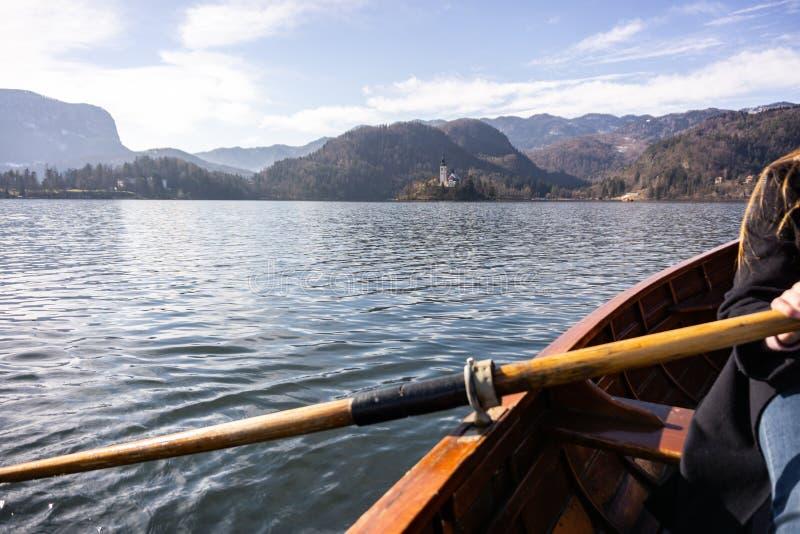 Mujer joven usando la paleta en un barco de madera - Eslovenia sangrada lago que rema en los barcos de madera fotos de archivo