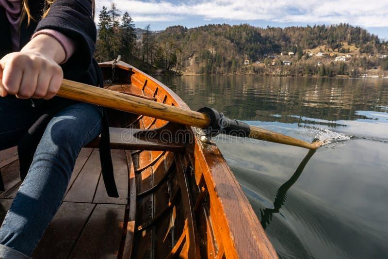 Mujer joven usando la paleta en un barco de madera - Eslovenia sangrada lago que rema en los barcos de madera fotografía de archivo libre de regalías