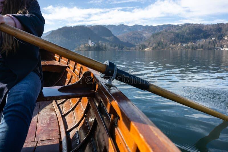 Mujer joven usando la paleta en un barco de madera - Eslovenia sangrada lago que rema en los barcos de madera imagenes de archivo