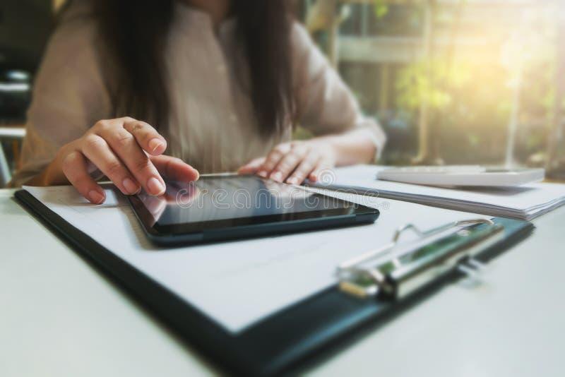Mujer joven usando la tableta mientras que trabaja en café imagenes de archivo
