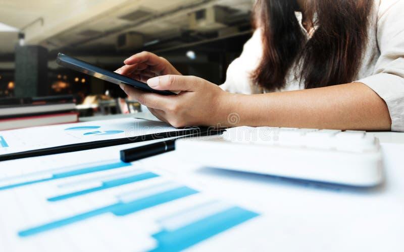 Mujer joven usando la tableta mientras que trabaja en documentos de los datos imagen de archivo