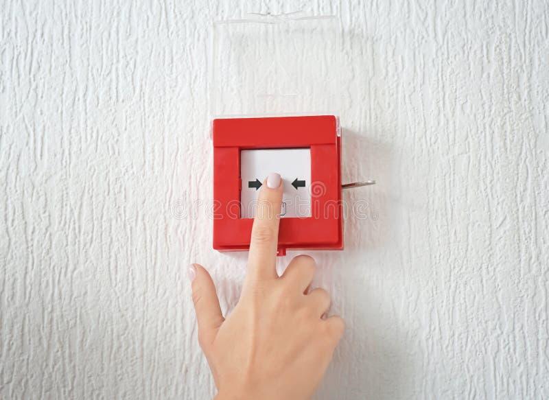 Mujer joven usando sistema alarma de incendio dentro fotos de archivo