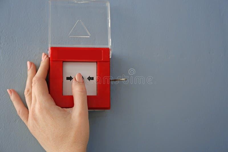 Mujer joven usando sistema alarma de incendio dentro imagen de archivo