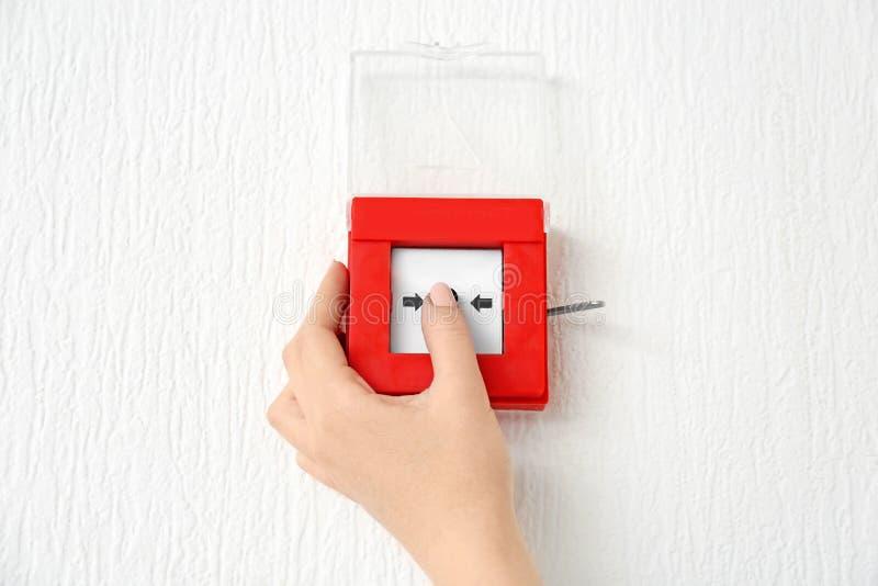 Mujer joven usando sistema alarma de incendio dentro imagen de archivo libre de regalías