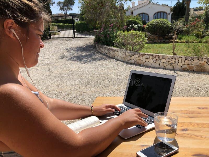 Mujer joven usando un ordenador portátil al aire libre fotografía de archivo libre de regalías