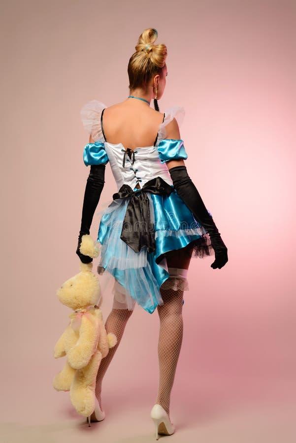 Mujer joven vestida como Alicia en el país de las maravillas, con un conejo en las manos que retroceden fotos de archivo