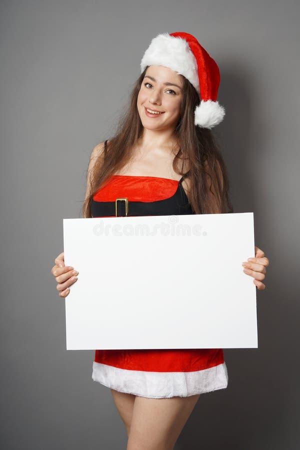 Mujer joven vestida en el traje de la Navidad y el sombrero de santa que presentan la muestra en blanco con el espacio de la copi imagenes de archivo