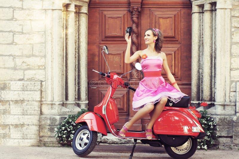 Mujer joven y atractiva con una vespa de motor - imagen retra del estilo imagen de archivo