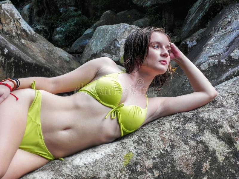 Mujer joven y atractiva en un traje de baño verde en una cascada hermosa fotos de archivo libres de regalías