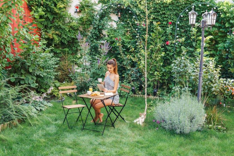 Mujer joven y atractiva que desayuna la mañana en jardín verde imagenes de archivo